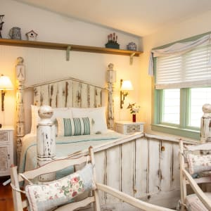 Queen sized bed with a large frame made of antique reclaimed fence posts.  There are bedside lamps, side tables, and windows