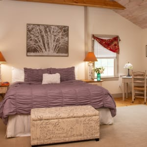 Photo of the Loft Suite king sized bed with white bedspread and lamps on bedside tables