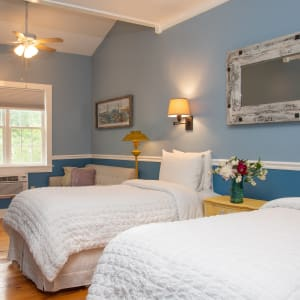Two twin beds in the Twin Maple have floral prints; the window and armoire can be seen in the background.