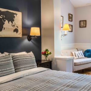 Queen sized bed with a blue and white bedspread and a dark blue wall behind.  In background is a small sofa next to a window.
