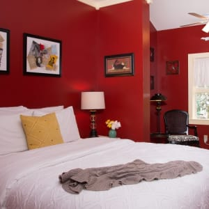 Queen sized bed in the Red Maple room with a white bedspread and pictures hanging in the red walls.