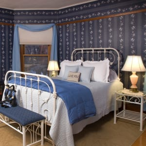 Country room with white iron bed and blue wallpaper