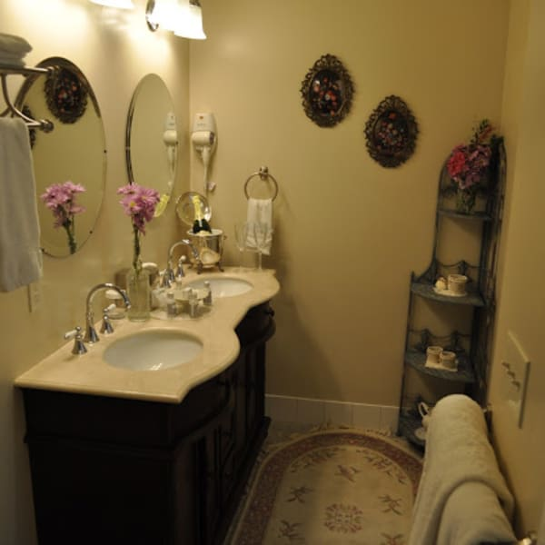 Private bathroom features double sink vanity with marble top