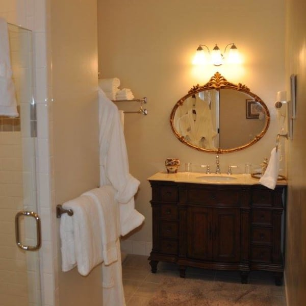 Private spacious bathroom, feature custom tile shower, antique cabinet vanity with marble top