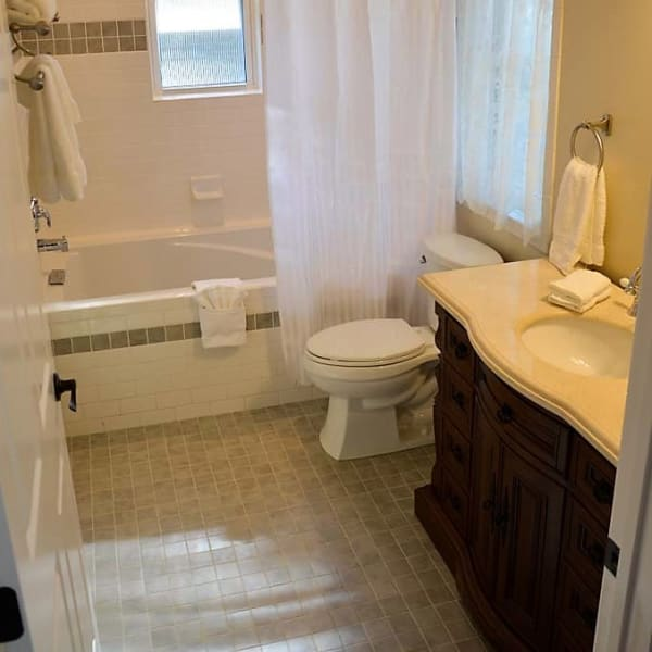 Private Bathroom features a deep soaking tub, antique marble vanity sink, custom tile tub/shower, tile floors