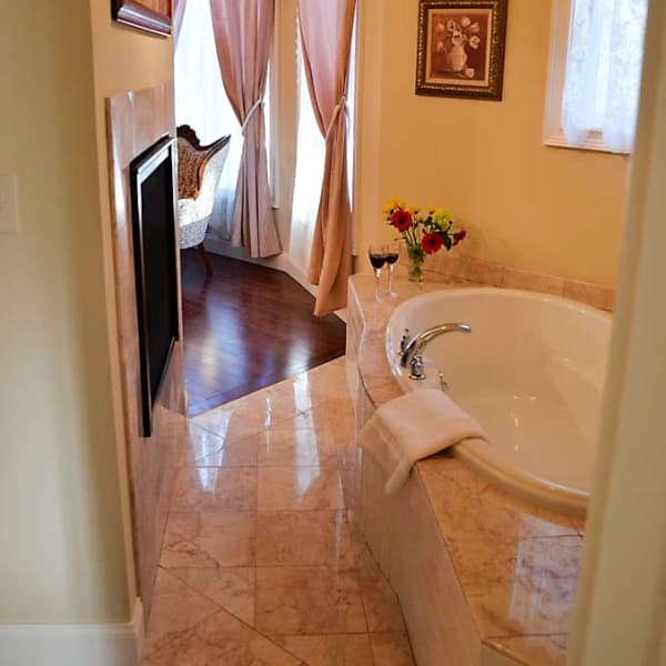Tandem deep soaking tub with cusstom marble surround and fireplace
