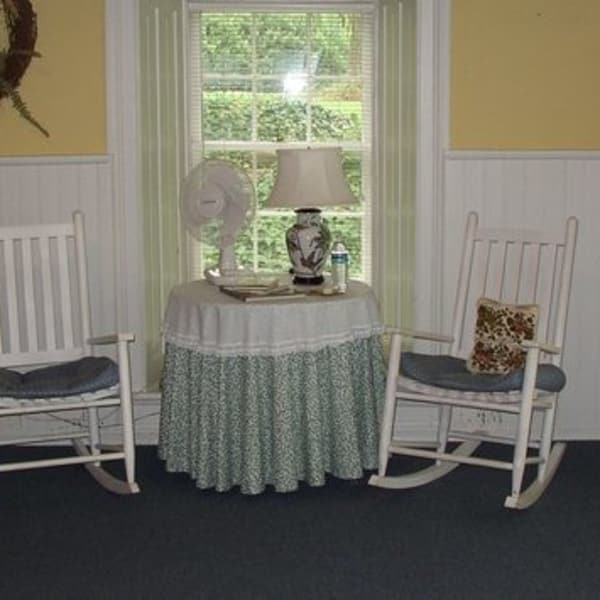 Garden Room sitting area with two rocking chairs, table and lamp in fromt of window overlooking gardens