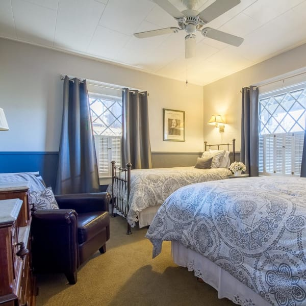 Queen bed and twin bed, ceiling fan, and windows