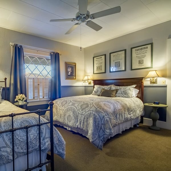 Queen bed and twin bed, ceiling fan, and window