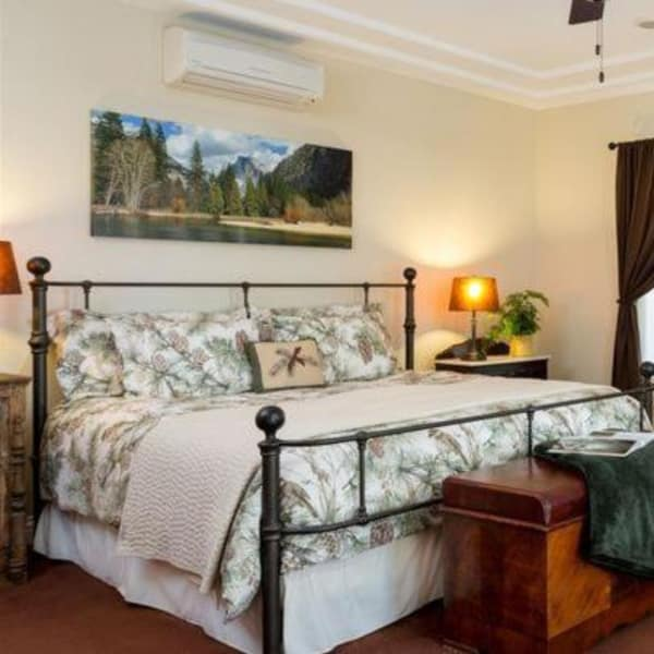 A large bed in the Brameberry Room with beautiful artwork of Yosemite National Park