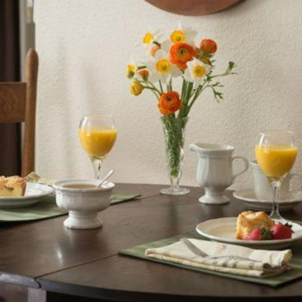Breakfast with orange juice setup for two and decorated with flowers