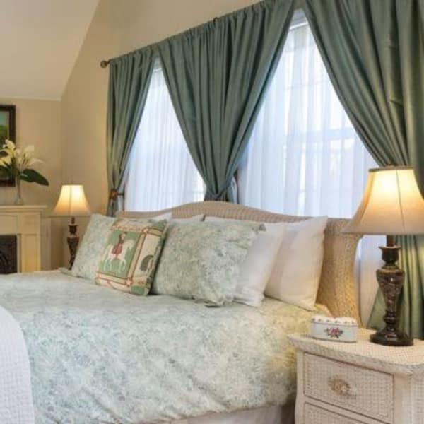 A cozy bed with warm lighting in the Briar Rose Room