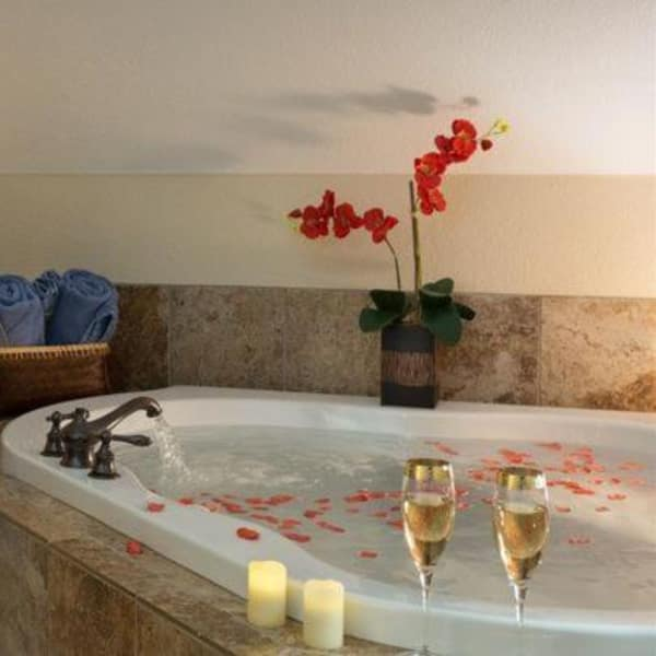 Two champagne flutes and some fresh flowers beside a jacuzzi tub