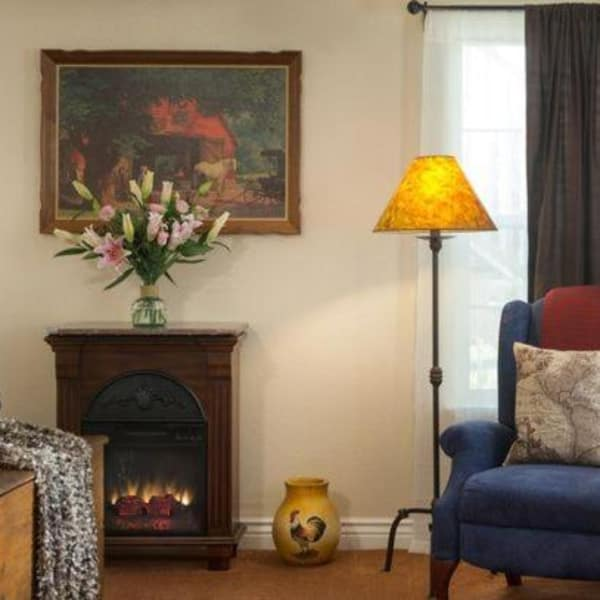Living area of the Half Dome suite complete with fresh flowers, artwork and a fireplace