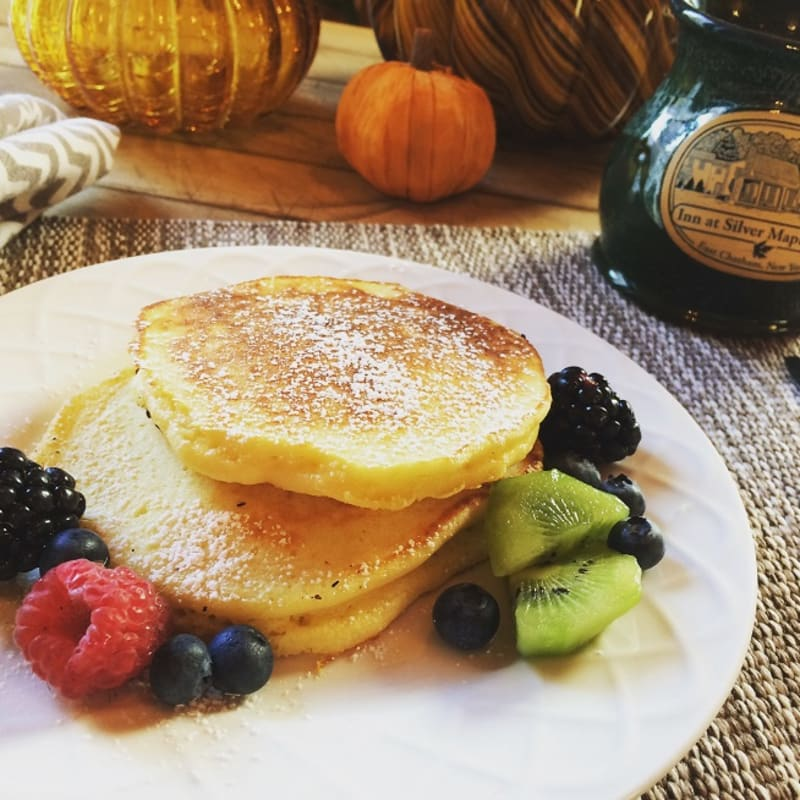 Plate of pancakes with berries and coffee