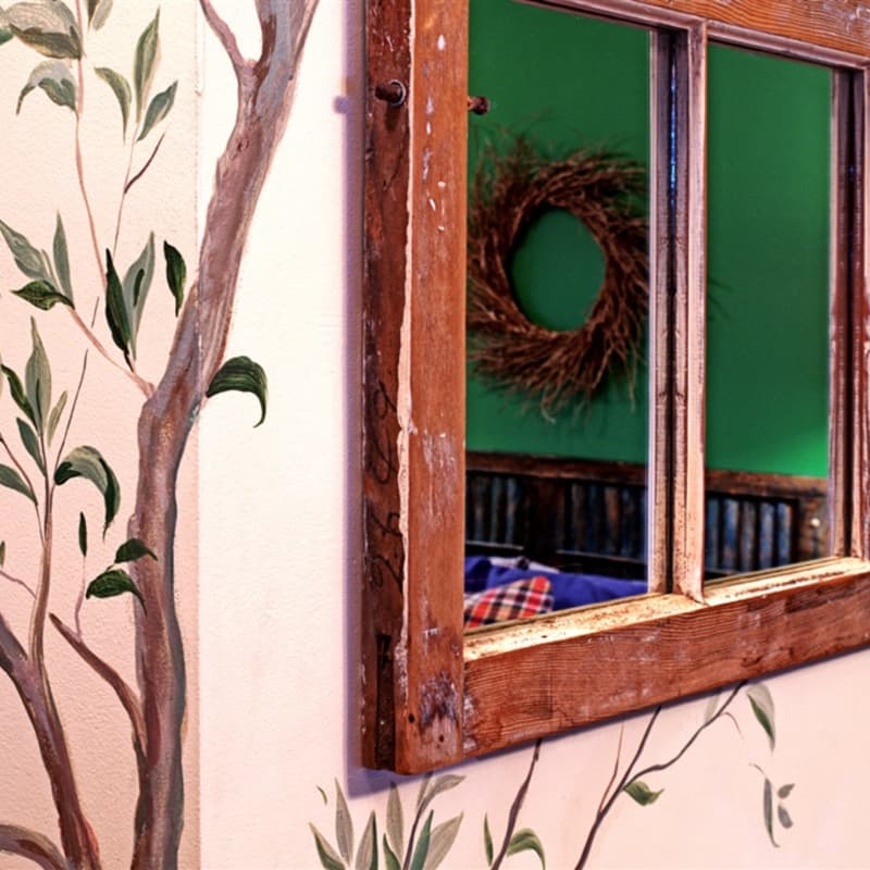 The Lower Lodge room has a pretty tree mural painted on the wall and a reclaimed window mirror.