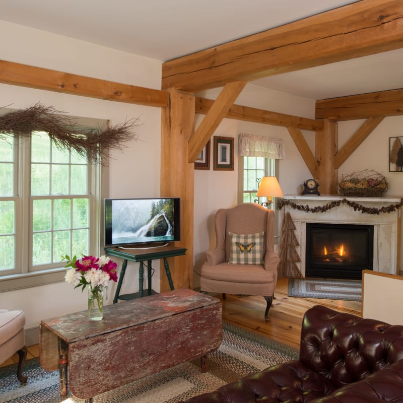 Downstairs living room of the Pines Duplex Suite with a TV, fireplace, brown leather sofa, and two wing chairs.