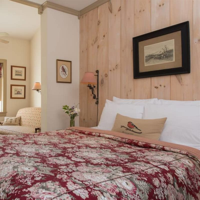 Queen bed with red floral print bedspread in front of a pine paneled wall in the Silver Maple Room.