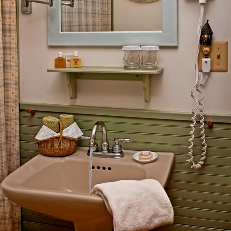 Pedestal sink of the Cottage Room with water flowing, a basket of washcloths, and shampoo,, soap, and other guest amenities.