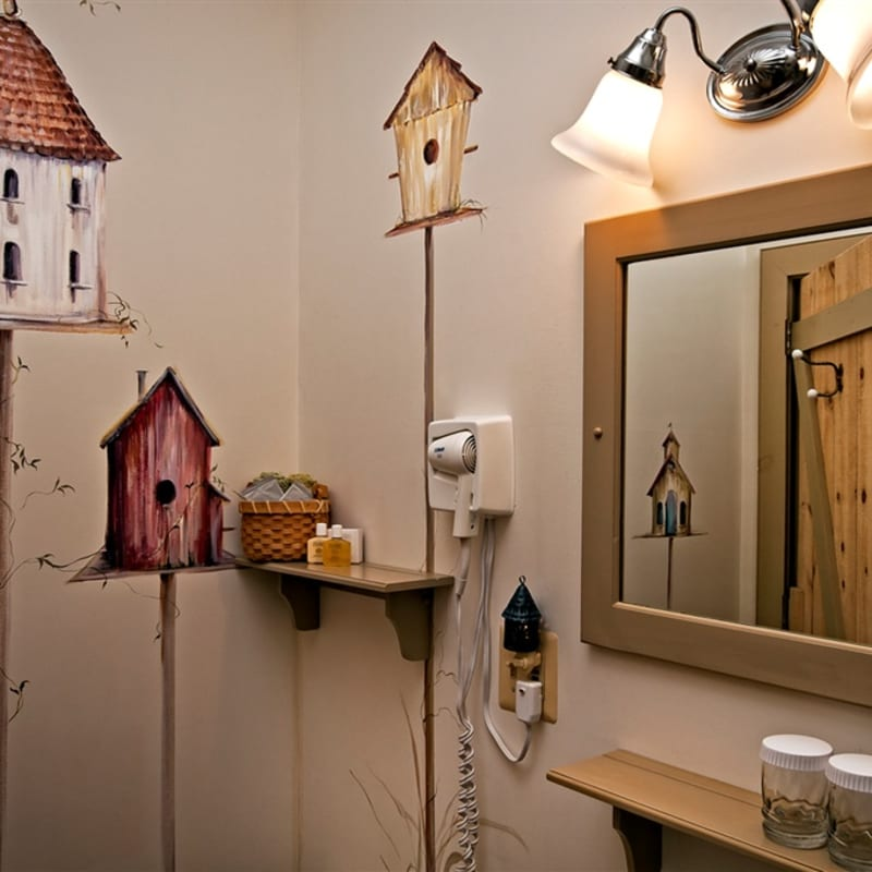 Pretty birdhouse murals on the wall of the bathroom in the Silver Maple room.