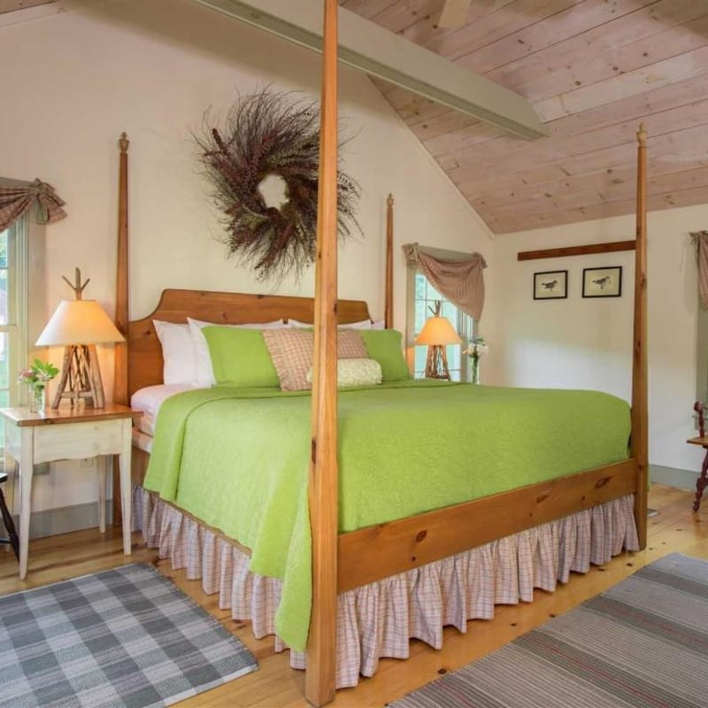 Photo of king sized bed in Pines Duplex Suite with a green bedspread