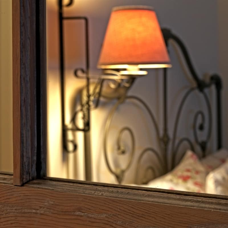 Photo of mirror showing reflection of bedframe and lamp in Sapling room
