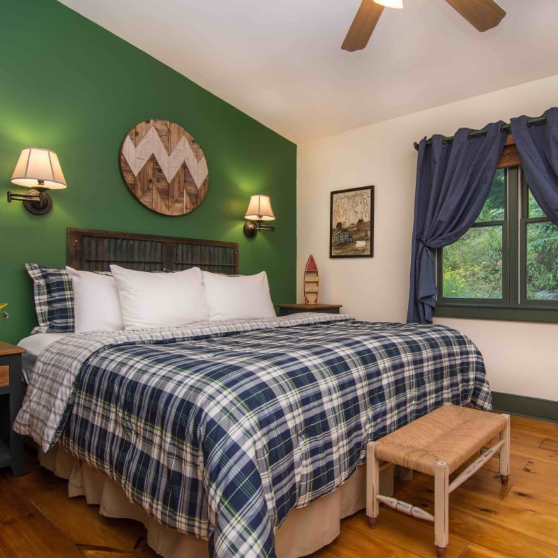 King sized bed in the Lower Lodge room with a blue and green plaid bedspread and a green wall behind the bed.  There are lights on each side of the bed, a small bench, and windows with blue curtains and wooden blinds.