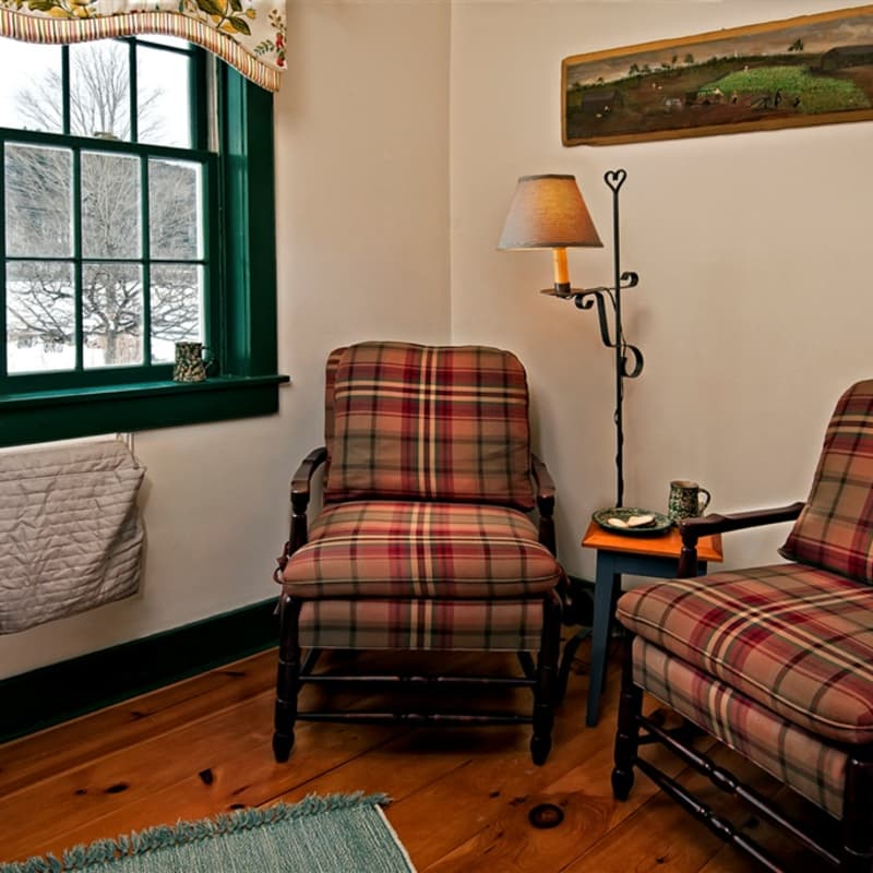 Two chairs and a lamp and side table next to the windows in the Twin Maple room.