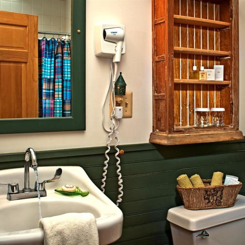 The bathroom of the Lower Lodge room sink and shelves.  There is a hair dryer and a basket of washcloths and make up remover.