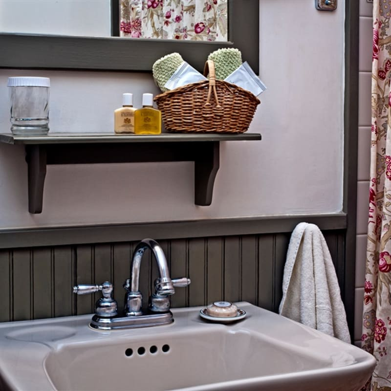 Sink in bathroom of Sapling Room with basket of washcloths, small shampoos, soap, and towels
