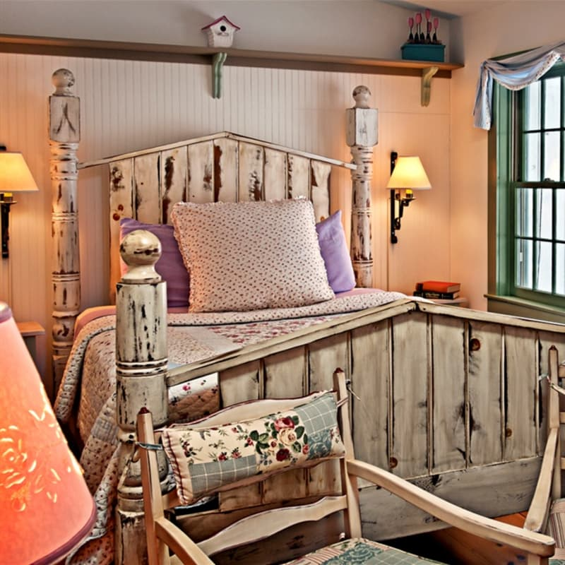 Queen sized bed with a large frame made of antique reclaimed fence posts.  There are bedside lamps, side tables, and windows.