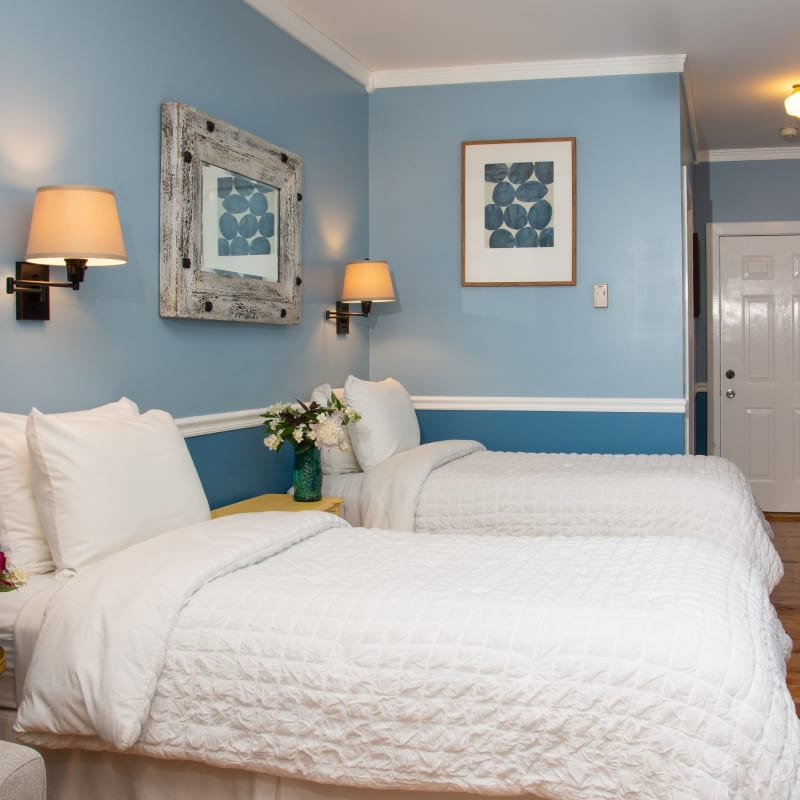 Two twin beds with white bedding and blue two tone walls