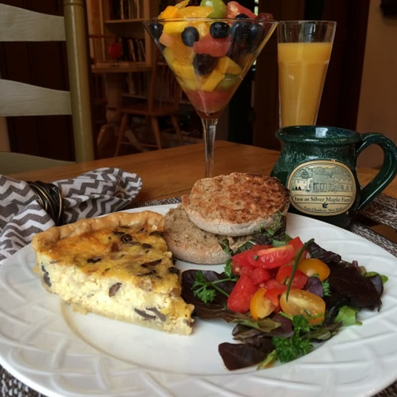 Breakfast plate with quiche, muffin, and salad, with a napkin, fruit salad, and glass of orange juice