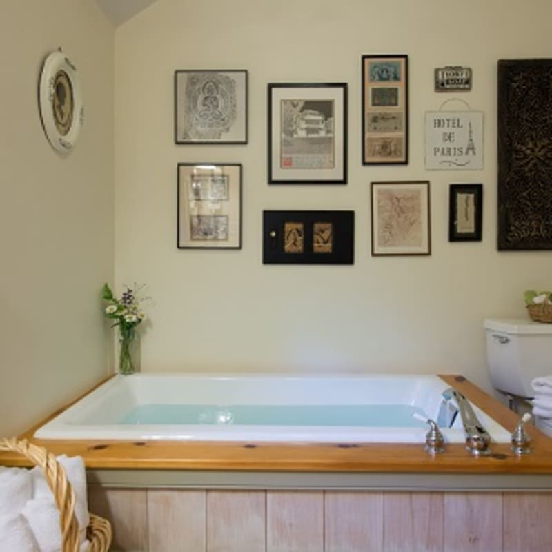 Soaking tub in the Pines Suite Duplex bathroom with a collage of international pictures mounted on the wall above.