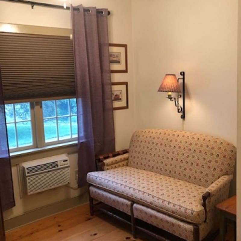 Small settee next to the windows in Silver Maple Room; there is an air conditioner.