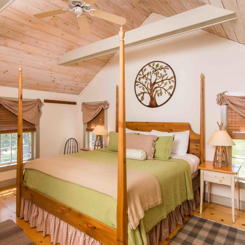 Four posted bed with green bedspread in the Pines Suite; a pine paneled cathedral ceiling with beams and windows.