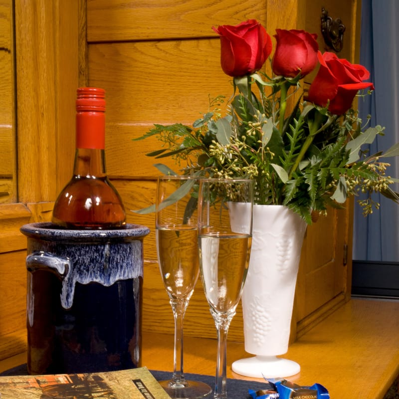 Wine bottle in ice bucket with red roses in white vase