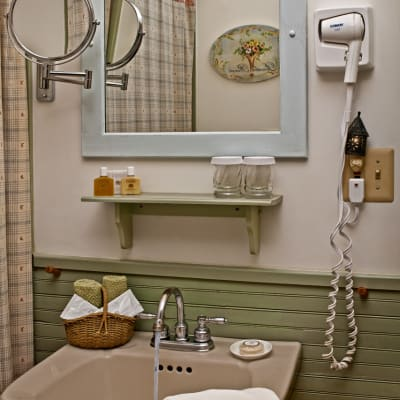 Photo of bathroom sink with water running, small basket with washcloths, shampoo, and soap.  A hairdryer and a magnified make u p mirror are mounted on the wall.