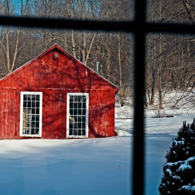 A view of a small red barn taken from indoors.  The ground is covered with snow and the trees in the distance are bare of leaves - it is a winter scene.