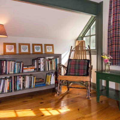 A small bookcase full of books and a rocking chair with a plaid printed pillow.