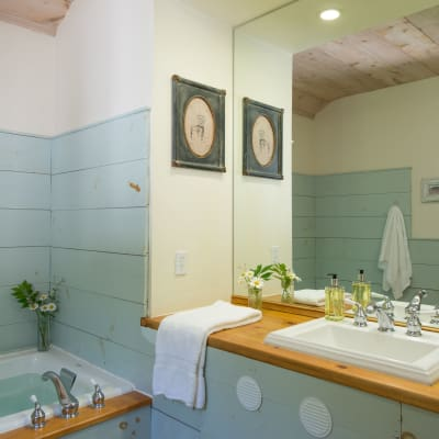 Photo of the bathroom sink and counter of the Loft Suite; blue and white walls and a large mirror.