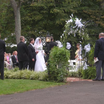 Ceremony at end of 90 foot front walk under floral decorated arch