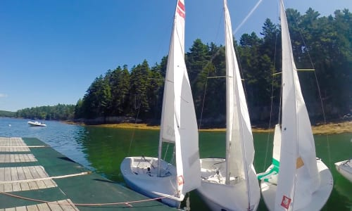 small sailboats next to dock